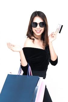 白い背景で隔離の買い物袋を持つ幸せなアジア女性
