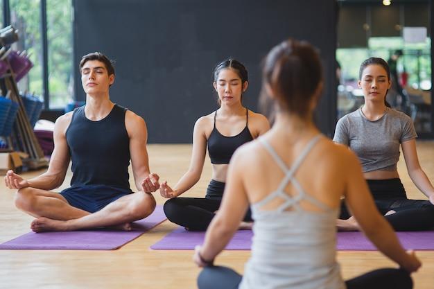 フィットネスクラブで健康的なライフスタイルのために一緒に瞑想ヨガを練習するミックスレースの人々のグループ