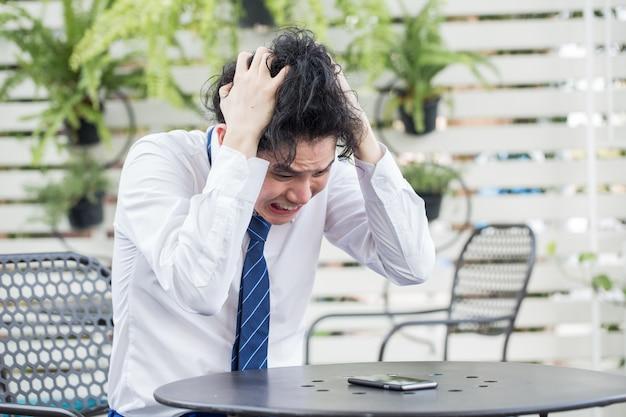 欲求不満の若いアジアのビジネスマンは絶望感に失敗しました