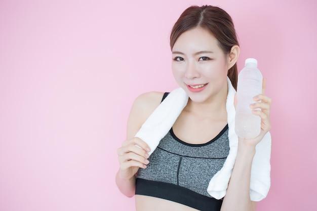 Молодая красивая азиатская девушка чистая свежая кожа, держа бутылку воды