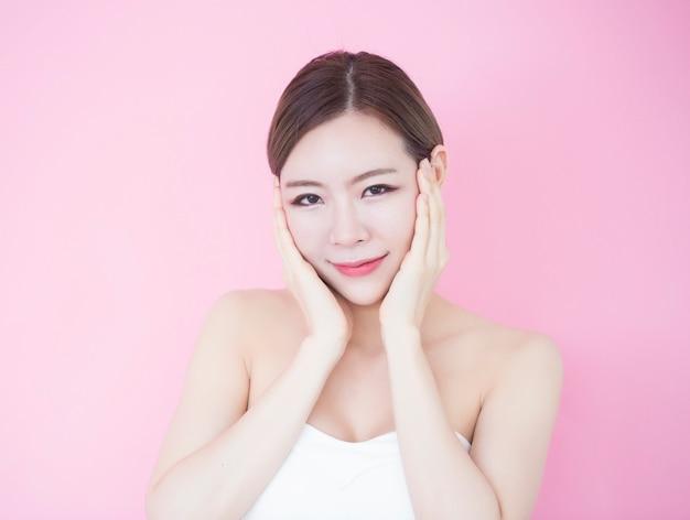 美しい若い白人アジア女性は彼女のきれいな新鮮な肌の顔に触れる