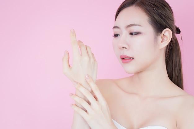 若い美しいアジアの女性の肖像画は彼女のきれいな新鮮な肌の顔に触れる