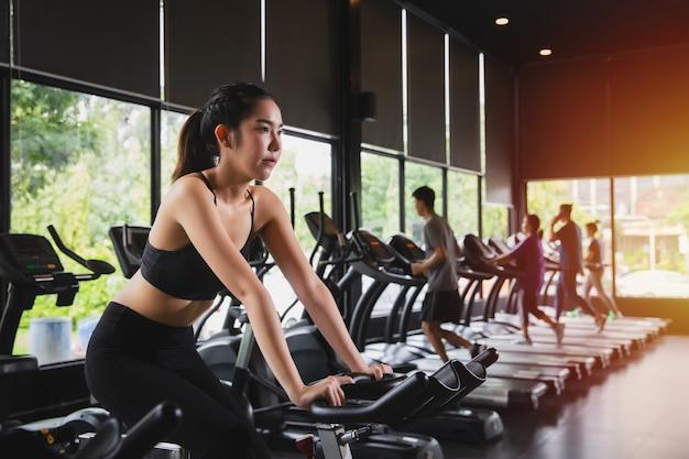 ジムでエアロバイクでトレーニングを実行しているスポーツウェアを持つ若い白人女性
