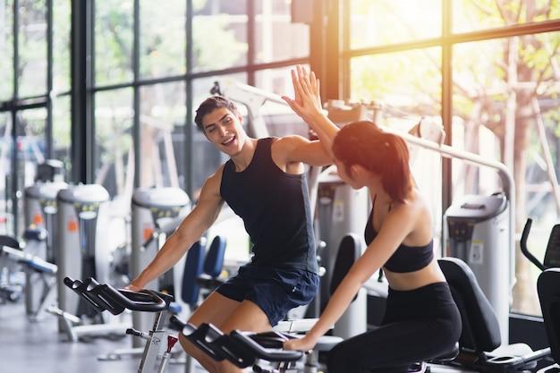 Здоровая женщина и мужчина в спортивной одежде бегают, давая друг другу высокие пять во время тренировок в тренажерном зале