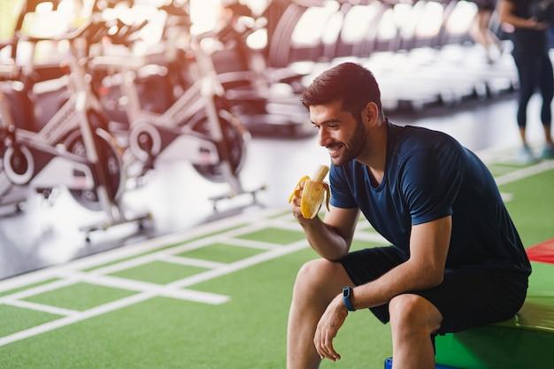 フィットネススタジオでのトレーニングの後バナナを食べる男