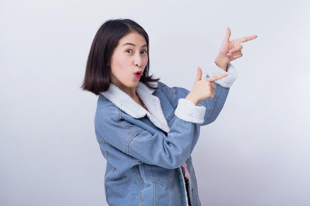 白人の笑顔の女性が背景、青いカジュアルな服の肖像画を着て肯定的な幸せな若いアジアの女の子で彼女の手を指す