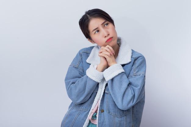 白人の笑みを浮かべて女性思考、悪い感情青いカジュアルな服の肖像画を着ている若いアジアの女の子