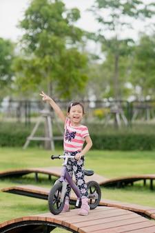 少し幸せなアジアの子供女の子が遊び場で自転車に乗る