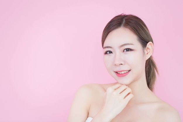 白人のアジア女性は彼女のきれいな新鮮な肌の顔に触れます。美容、スキンケア、整形手術、スパ療法の概念