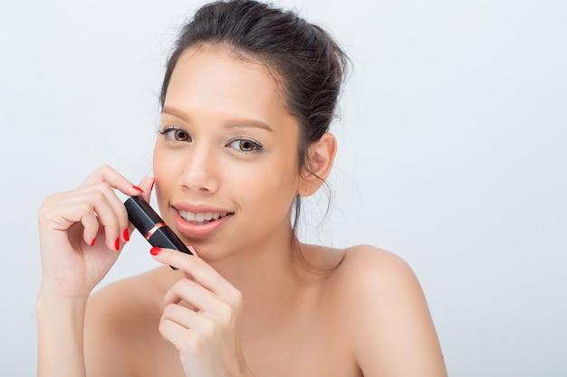 Крытый студийный снимок для красивой азиатской женщины, широко улыбающейся, применяя помаду с красотой природы макияж свежая мягкая кожа