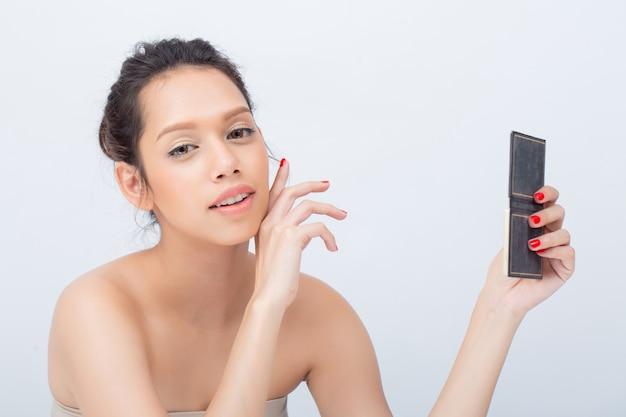 Крытый студийный снимок красивой азиатской женщины, улыбаясь, применяя палитру теней для век с природой красоты макияж свежей мягкой кожи