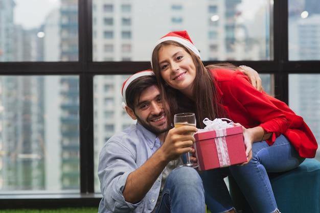 若いカップルが楽しんで、サンタ帽子をかぶっているギフトボックスを保持しているクリスマスパーティーと恋に