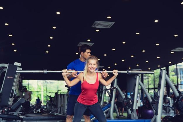 バーベルを持ち上げるスポーティな女の子とジムで運動を教えるトレーナーアジア人