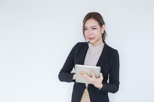 Усмехаясь молодая азиатская бизнес-леди с технологией таблетки с космосом экземпляра