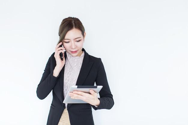Усмехаясь молодая азиатская бизнес-леди с технологией таблетки и умный телефон с космосом экземпляра