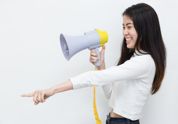 Молодая азиатская женщина крича и крича с мегафоном на белой предпосылке с космосом экземпляра