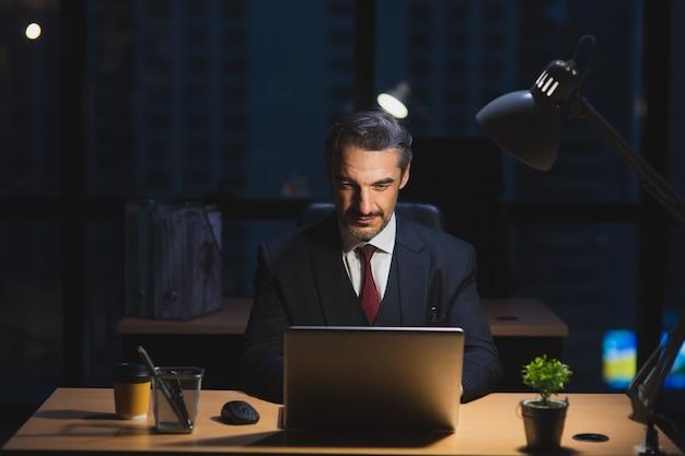 夜のオフィスでコンピューターのラップトップで遅く働く白人のビジネスマン。マネージャーチェックノートブック、夜遅くまで働いて、残業の概念から会社のレポート