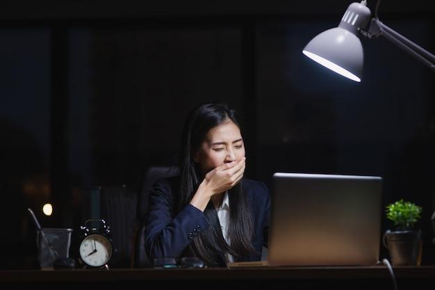夜オフィスで眠そうな机の上に座って遅く働くアジアの秘書の女の子。疲れて疲れたビジネスウーマンは会社のために一生懸命働く