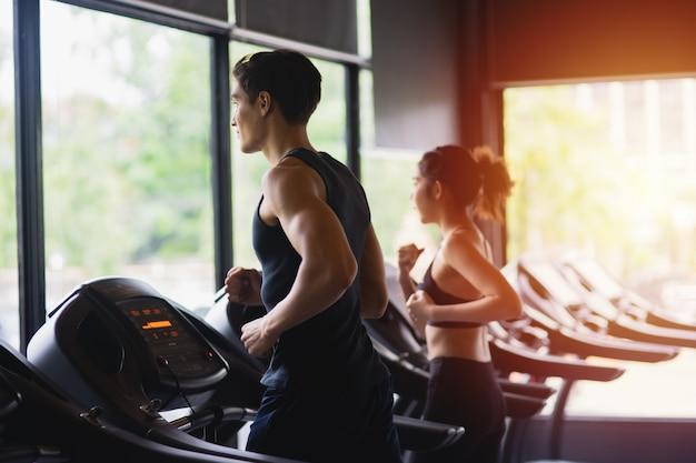 健康な女性とジムスポーツ、ボディービル、ライフスタイル、人々の概念で運動トレーニングを実行しているスポーツウェアを持つ男