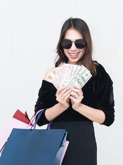 ショッピングバッグとお金を持って幸せなアジアの女性