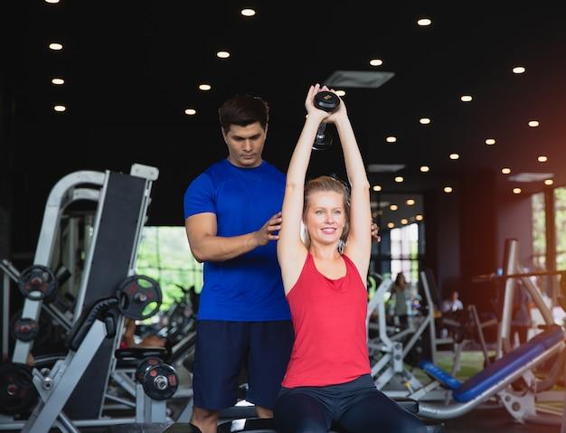Усмехаясь гантель и тренировка кавказской женщины поднимаясь в спортзале с преподавательством человека тренера или инструктора азиатским. пятнистая девушка, использующая руку для силовых тренировок, в то время как личный тренер контролирует ее прогресс