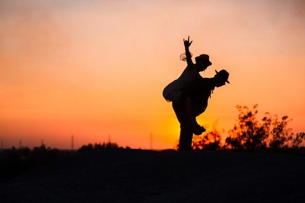 丘の上に新郎新婦。自然の森、夕日とシルエットの結婚式のカップルでの結婚式でカップル新婚夫婦