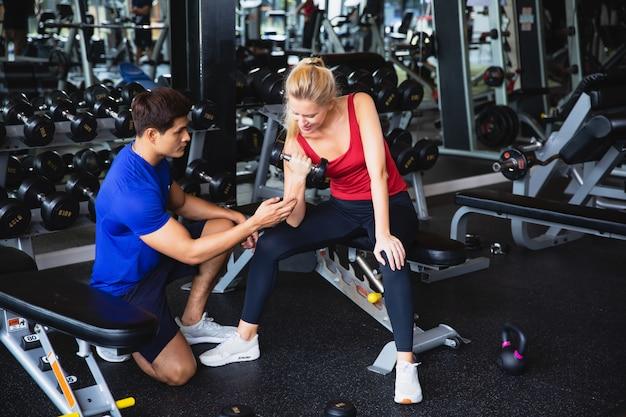 Кавказская женщина подъема гантелей и упражнений в тренажерном зале с тренером или инструктором азиатских человек преподавания. пятнистая девушка, использующая руку для силовых тренировок, в то время как личный тренер контролирует ее прогресс