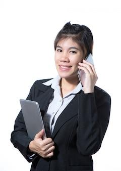 ビジネスの女性がコンピューターのタブレットを保持していると携帯電話で話しています。
