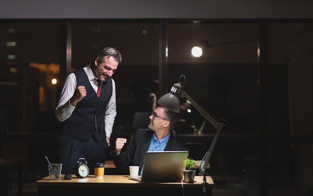 Два бизнесмена чувствуют себя счастливыми и успешными после работы допоздна в офисе.