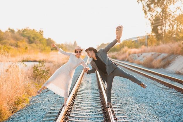 流行に敏感な新郎新婦の幸せな笑顔と鉄道を歩きながら笑う