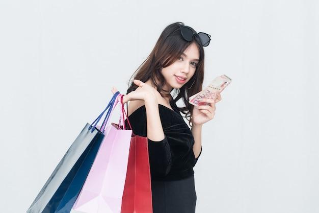 ショッピングバッグとお金を保持している幸せなアジアの女性