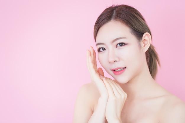 アジアの女性は彼女のきれいな顔に触れる