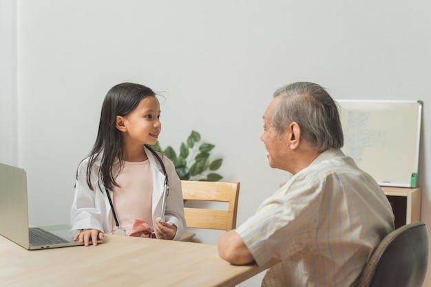 Внучка играет доктора, используя стетоскоп, проверяя дедушку в гостиной