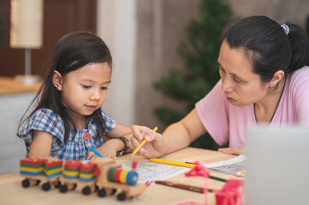 Мать учит домашнее задание и разговаривает с дочерью, чтобы учиться
