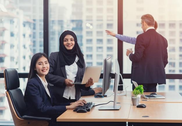 オフィスでの会議中に会議室で共有および一緒に議論する多世代ビジネス人々のグループの成功チームワーク