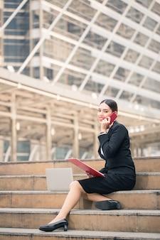 スマートフォンを使用して現代の笑顔の美しいビジネス女性