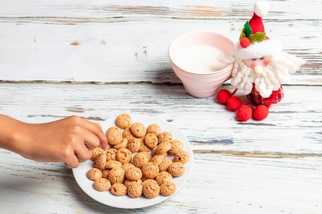 Милая маленькая девочка играет с печеньем и молоком санты на рождество
