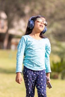 公園で彼女のヘッドフォンでスマートフォンで音楽を聴く少女
