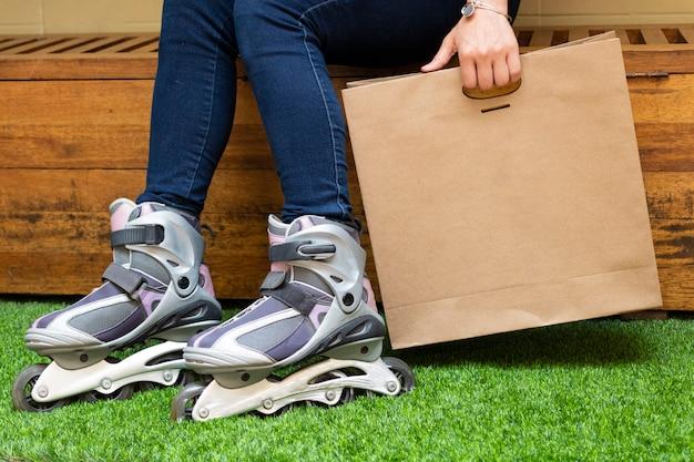 紙袋に食べ物を提供するローラースケートの若い女性