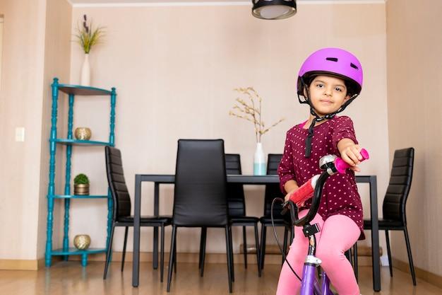 自宅で彼女の自転車に乗って幸せな自転車のヘルメットを持つ少女