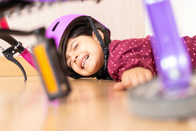 Грустная маленькая девочка упала на землю, играя со своим велосипедом в доме