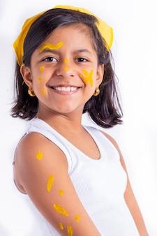 黄色の日を祝うために彼女の顔を描いた幸せな少女