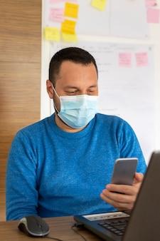 彼の電話を使用して医療マスクを持つ若者