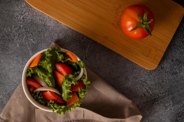 灰色の背景に白いボウルの中のサラダのトマト