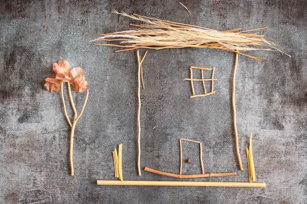 灰色の背景に植物の小枝で作られた家