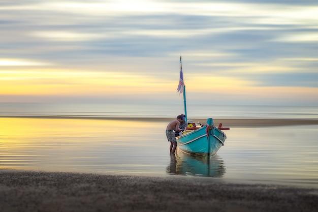 Рыбацкая лодка и рыболов на морском побережье с небом утра.