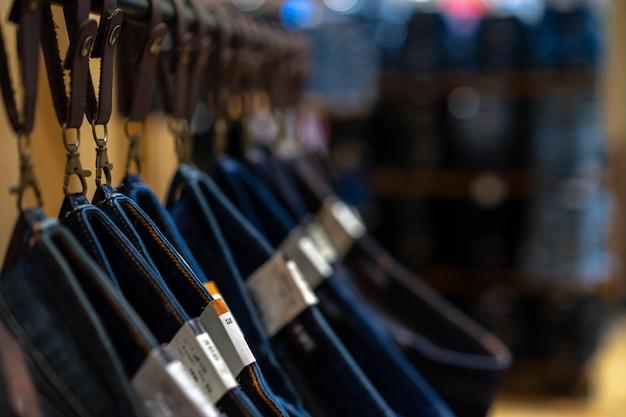 Многие джинсы висят в магазине.