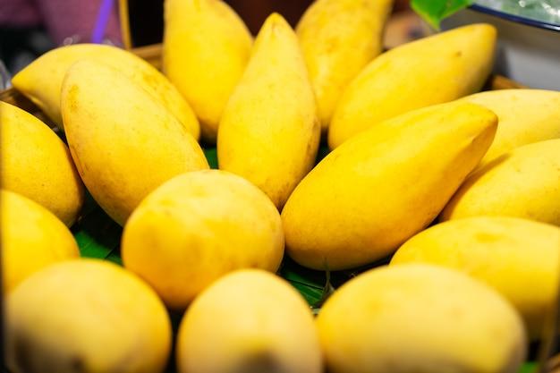 バスケットの新鮮なマンゴーはおいしい味。有機市場でのエキゾチックな果物。有機果実