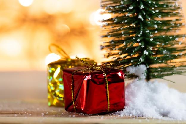 ギフトと光のボケ味の背景を持つ白い雪の上のクリスマスツリー