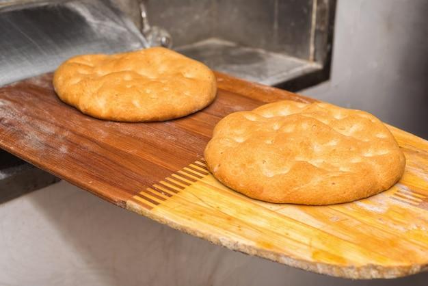 オーブンからパンを出してください。焼きたてのパン、ショベルで取り出したもの。